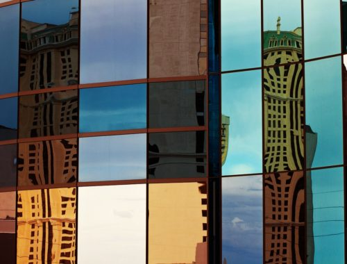 Reflection of buildings on the glass wall of another building